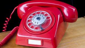 Röd trådtelefon från sjuttiotalet på ljusbrunt träbord.