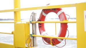 En frostig livboj på en färja med gula detaljer.