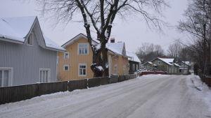 Väg med snö och trähus.