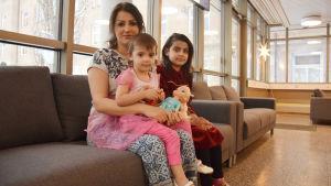 En mamma och två av hennes barn sitter i en soffa
