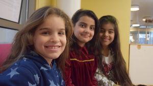 tre flickor sitter på rad i en soffa och ler.