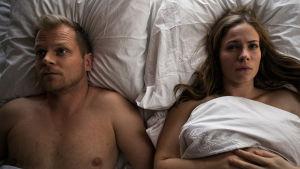 Pihla Viitala ja Antti Luusuanniemi makaavat sängyssä vierekkäin ja katsovat molemmat ylöspäin.