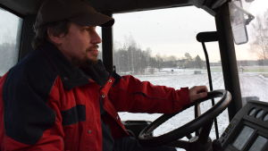 Anders Abrahamsson sitter i traktorhytten, vinterlandskap utanför.