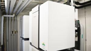 Fyrkantiga vita maskiner eller behållare i ett litet rum.