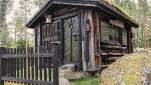 """Liten stuga med mossigt tak, ovanför dörren står det """"Björnidet""""."""