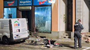 Ett krossat skyltfönster och en polisbil framför.