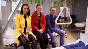 Kseniya Popov, Sara Kinnunen ja Eldar Jandahanov istuvat hoitoluokassa hoitosängyn päällä ja hymyilevät kameralle.