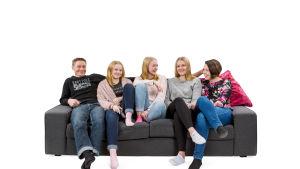 Kuvassa Mika, Veera, Olivia, Annika ja Susanna istuvat sohvalla.