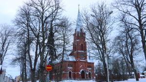 En röd tegelkyrka i Kristinestad skymtar genom träden. Marken är vit av snö.