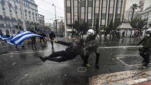 Demonstrant släpas bort av polis i Aten under demo mot namnavtalet med Makedonien. 20.1.2019.