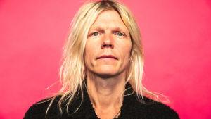 Jori Sjöroos katsoo kameraan lähikuvassa pinkin taustan edessä.
