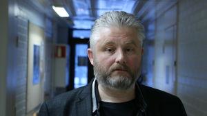 En medelålders man med grått kort hår och skägg står i en korridor.