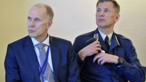 Två blåklädda män sitter bredvid varandra.
