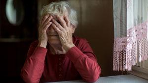 en äldre kvinna i röd blus håller händerna på ansiktet. Sittter vid köksbord bredvis gardin med ljusröd spets