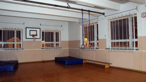 En liten gymnastiksal med basketställning och blåa madrasser.