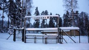 En grind där det står Junkars. I bakgrunden syns en gul danspaviljong. Det ligger mycket snö på marken.