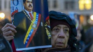 Pro Nicolas Maduro protest i Berlin i slutet av januari 2019. En demonstrant håller ett porträtt av Nicolas Maduro.