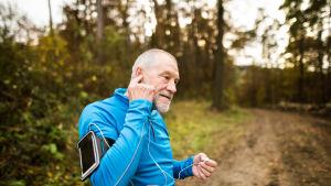Gråhårig man i träningskläder har stannat på vägen i en skog och lyssnar koncentrerat på nåt i hörlurar.