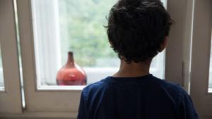 Mörkhårig pojke med blå blus. 9-10 år. Hans ansikte syns inte, bara ryggen. Han tittar ut genom ett fönster mot en gård.Rund brunaktig glasflaska i fönstergluggen.+