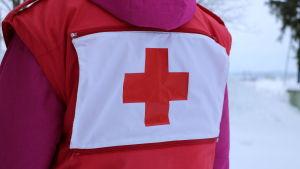 En röd väst med ett rött kors på ryggen.
