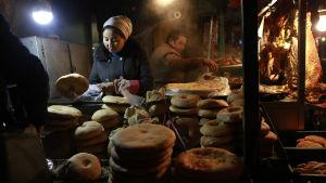 Uigurer säljer bröd på en marknad i Xingjiang, Kina