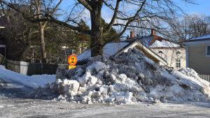 En stor snöhög täcker nästan trafikmärket.