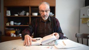 Ole Högberg sitter vid sitt köksbord och bläddrar i sin bok.