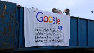Ett lakan hänger över ett lastbilsflak. På lakanet står det google, samt flera olika sökfraser på finska, som ska se ut som att man gjort olika sökningar på google.