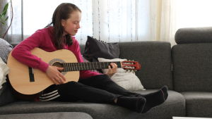 Nuori tyttö istuu sohvalla hiukset märkänä ja soittaa kitaraa.