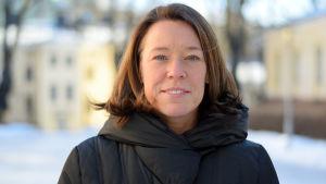 professor Åsa von Schoultz porträtt utomhus på vintern vid statsvetenskapliga fakulteten med gula byggnader oskarpt i bakgrunden.