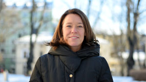 Professor i allmän statslära Åsa von Schoultz i vinterrock barhuvad på statsvetenskapliga fakultetens gård med ljusa byggnader och träd i bakgrunden.