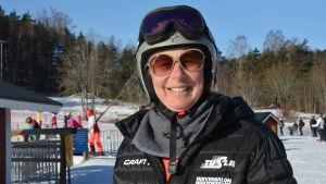 Skidläraren Sari Fahlbom, en dam med svart jacka, grå hjälm, solglasögon och skidglasögon.