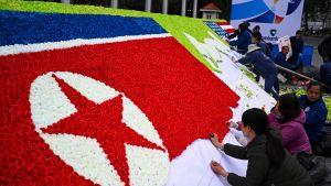 Nordkoreanska och amerikanska flaggor i papper tillverkas i Hanoi