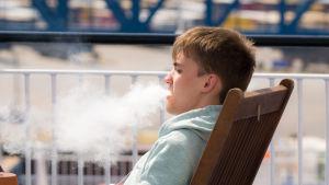 Person röker på balkong.
