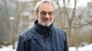 Profesor Mikel Hildén i blå jacka på Miljöcentralens gård med träd i bakgrunden på vintern.