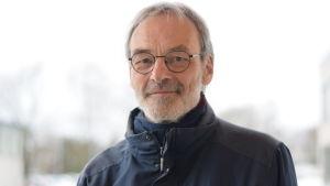 Professor Mikael Hildén med blå jacka och glasögon mot vit himmel.