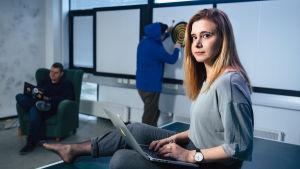 Laura kankaala istuu pöydällä tietokone sylissään.