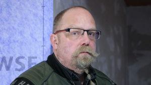 En man med glasögon och bockskägg står och lutar mot en blå vägg.
