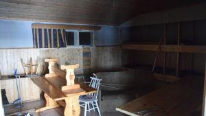 Ett bord i trä med en bänk över och en vit stol intill inne i en gammal trästuga. I bakgrunden en pass och sopborste och skyffel.