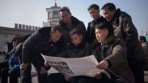 Folk läser tidning efter misslyckat toppmöte i Hanoi