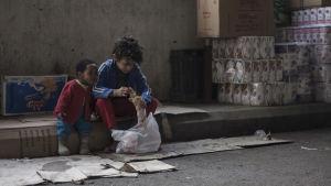 Två små barn sitter och på trottoaren och gräver i en påse.