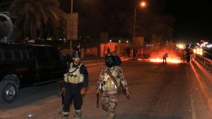 Irakiska poliser framför en brinnande barrikad i Basra