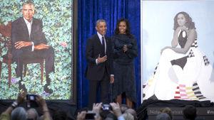 Storleende Barack och Michelle Obama på scen av sidan av de nymålade porträtten av dem i Washington DC.