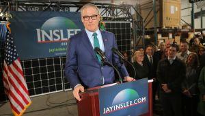 Jay Inslee i talarstol med publik och amerikansk flagga. Han kungjorde sin kandidatur på ett företag för solenergi.