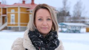 En kvinna med axellångt ljust hår står på en skolgård. Marken är täckt med snö.