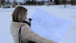 En kvinna med axellångt ljust hår visar upp en planritning på en byggnad.