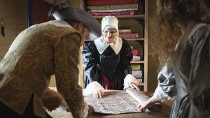 En kvinna i gamla kläder förevisar en rulle med spets på ett bord.