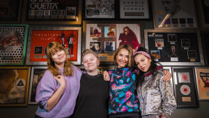 Vilma Alina, Minna Koivisto, Iisa ja Julia Rautio seisovat hymyillen kultalevyseinän edessä.