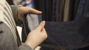 Outi Pyy pitää käsissään farkkujen lahjetta, jonka on kääntänyt nurin.
