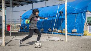 Ung kvinna i slöja spelar står vid ett fotbollsmål och sparkar en boll i ett flyktingläger.